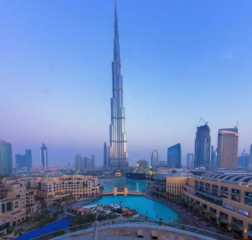 DXB Dubai Architecture Building Building Exterior Built Structure Burj Khalifa City Cityscape Clear Sky Financial District  Landscape Luxury Modern Nature No People Office Building Exterior Outdoors Sky Skyscraper Spire  Tall - High Tower Travel Destinations Water