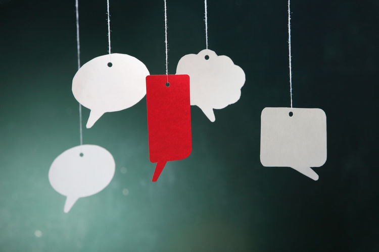 Close-up of speech bubbles hanging against wall