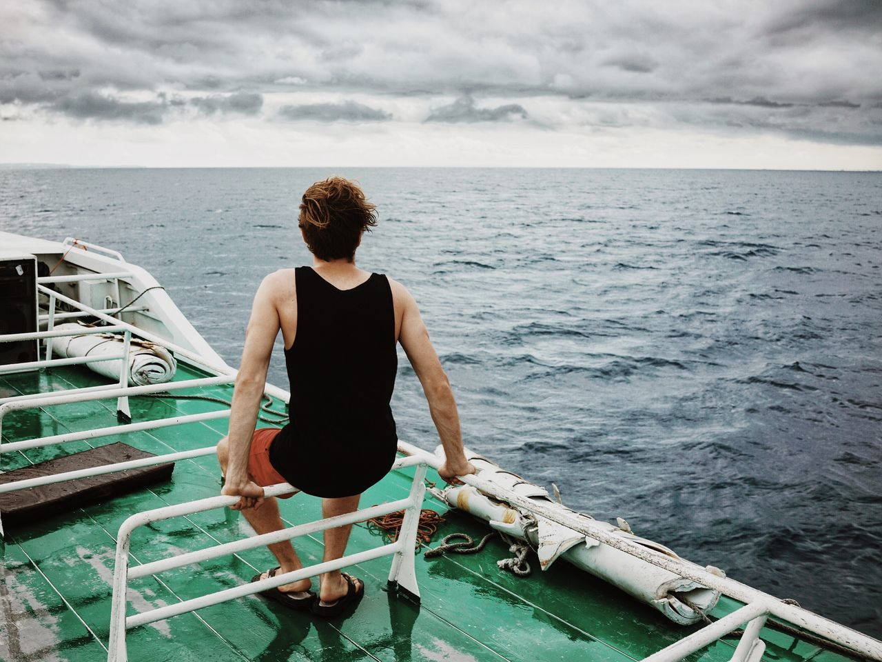 Rear view of man on boat at sea against cloudy sky