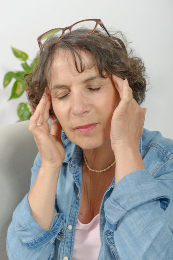 Mature woman suffering from headache at home