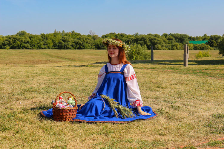 Young woman sitting with basket on field