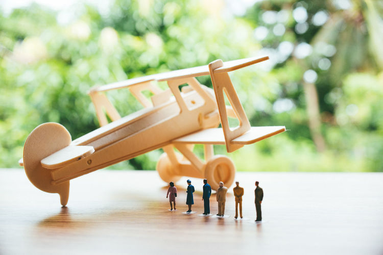 Close-up of toy airplane with figurines on wooden table against trees