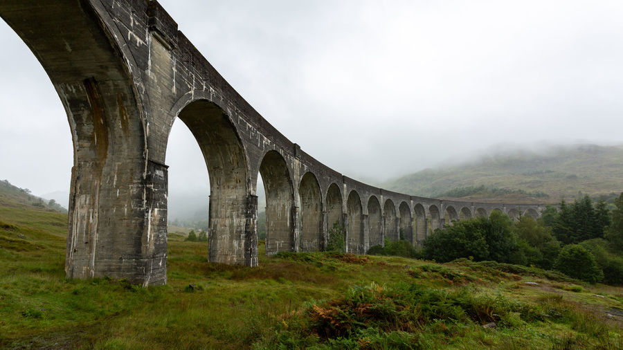 The famous Glenfinnan Viaduct in Scotland, also known as The Hogwarts Express from the movie Harry Potter. Glenfinnan Glenfinnan Viaduct Hogwarts Express Harry Potter Bridge Scotland Scottish Viaduct Movie Location Outdoors Nature Natural Travel Trip Explore Experience Beauty Beautiful Trekking Hiking Summer Season  Grass Green Clouds Hills Mountains Weather Landscape Tourism Tourist Attraction  Holiday Vacations