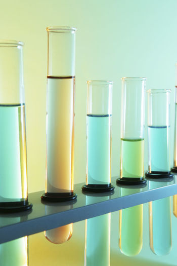 Close-up of test tubes in rack against colored background