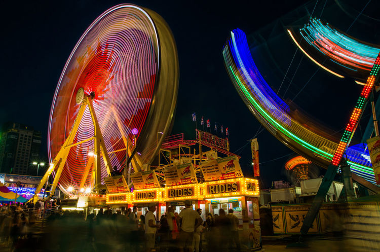 Amusement Park Amusement Park Ride Amusementpark Arts Culture And Entertainment Blurred Motion Canada Flag Cities At Night City City Life City Life Cityscapes Ferris Wheel Ferris Wheel Flag Illuminated Long Exposure Low Angle View Motion Motion Blur Multi Colored Multicolors  Neon Night Night Lights Nightphotography