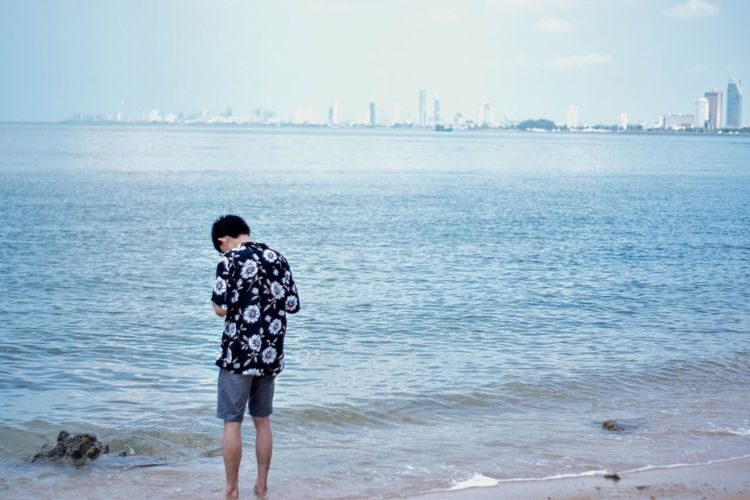 Water Sea Beach Land One Person Real People Day Nature Sky Leisure Activity Lifestyles Rear View Standing Beauty In Nature Three Quarter Length Scenics - Nature Looking At View Casual Clothing Outdoors Architecture