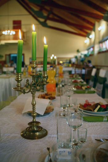 Three candles - Candles on the table waiting for the guests Banquet Brass Candle Candlestick Celebrate Decoration Design Dishes Drink Equipment Event Festive Flame Food Green Guests Hotel Knife Ornament Plate Restaurant Romantic Table Tablecloth Wedding