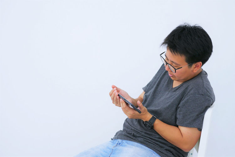 Short hair woman playing mobile phone while siting on chair. Casual Clothing Copy Space Eyeglasses  Front View Glasses Holding Indoors  Leisure Activity Lifestyles Men One Person Real People Sitting Studio Shot Three Quarter Length White Background Young Adult Young Men