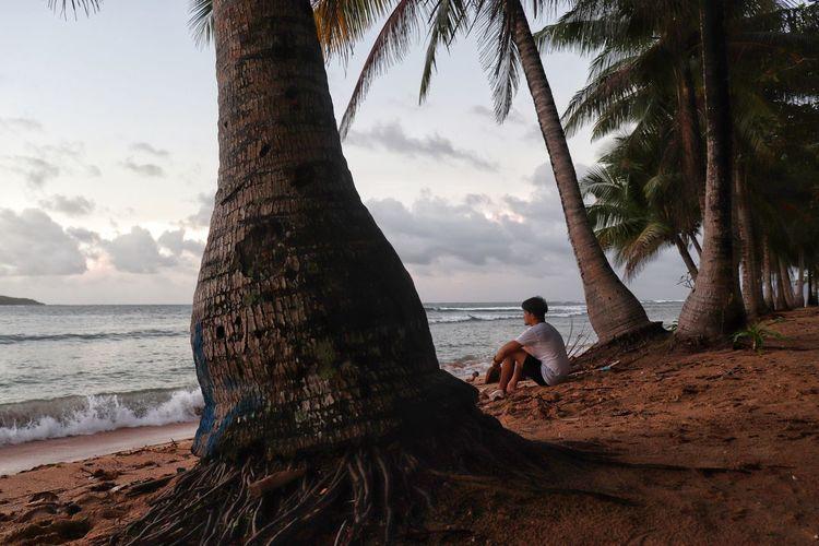 People sitting on beach by sea against sky