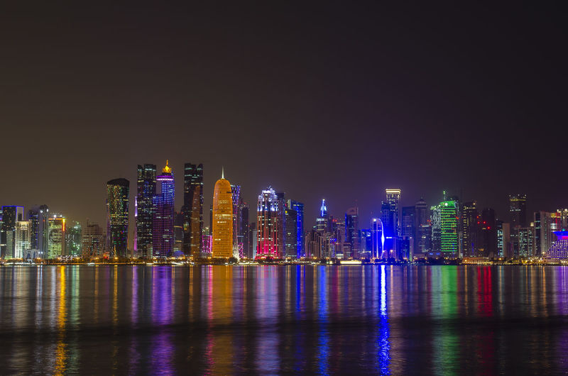 The skyline of the modern and high-rising city of Doha in Qatar, Middle East. - Doha's Corniche in West Bay, Doha, Qatar Building Exterior Built Structure Architecture Building Night Illuminated City Skyscraper Water Tall - High Urban Skyline Modern Landscape Cityscape Qatar Doha
