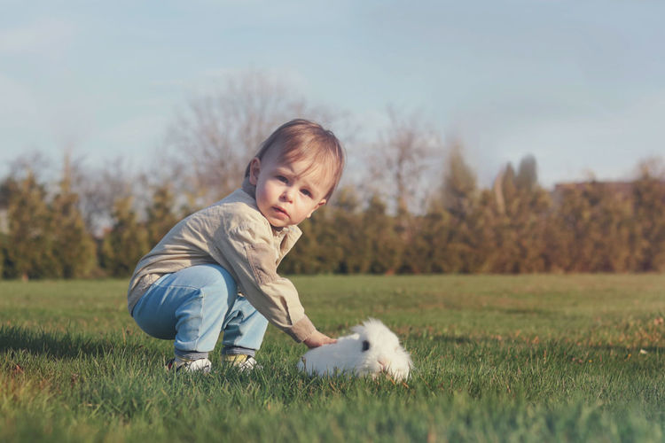 Cute baby boy and white fluffy bunny in the garden
