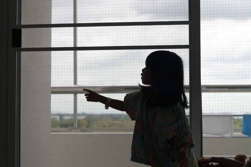 Side view of girl pointing while standing by glass window