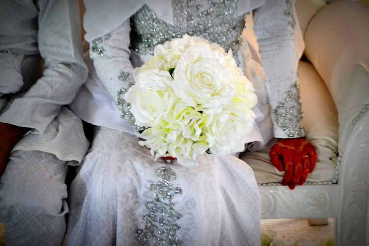 Low section of woman holding bouquet