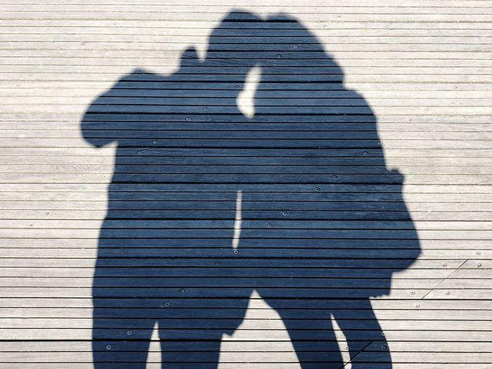 Shadow of couple on boardwalk