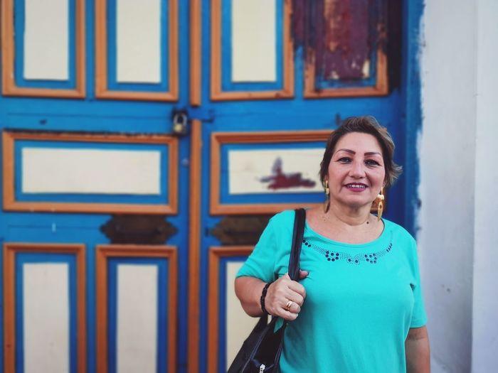 Portrait of smiling woman standing against blue door