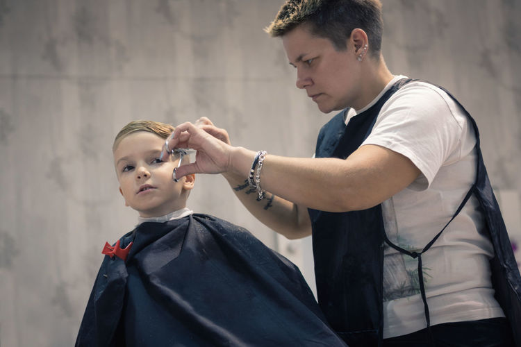 Two People Males  Child Real People Boys Childhood Young Adult Hairdresser Adult People Barber Hairstyle Human Hair Lifestyles Hair Salon Hair Stylist Barbershop Haircut Cutting Hair Styling Kid Boy Blond Hair Hairdressing Salon Caucasian Patience
