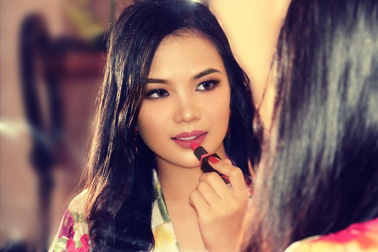 Close-up of young woman applying lipstick