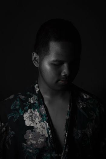 Close-up portrait of a boy against black background