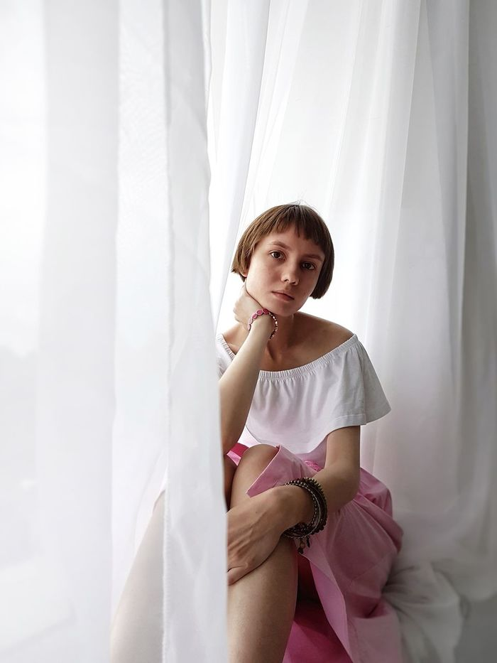 SMILING YOUNG WOMAN SITTING AGAINST CURTAIN IN SUNLIGHT