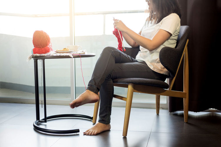 Low section of woman sitting on chair while knitting at home