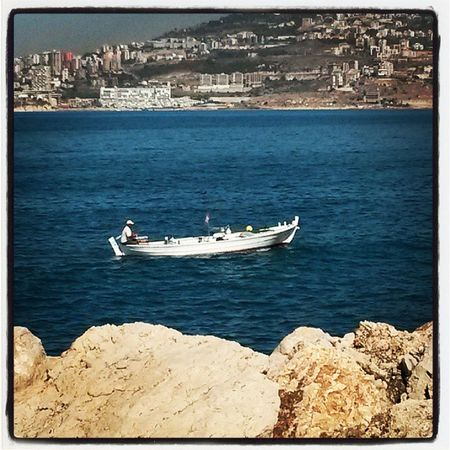 A Lovely Sea View from ATCL Lebanon. rocks boat fishing montain blue white beige