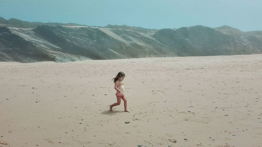 Side view of girl walking at sandy beach