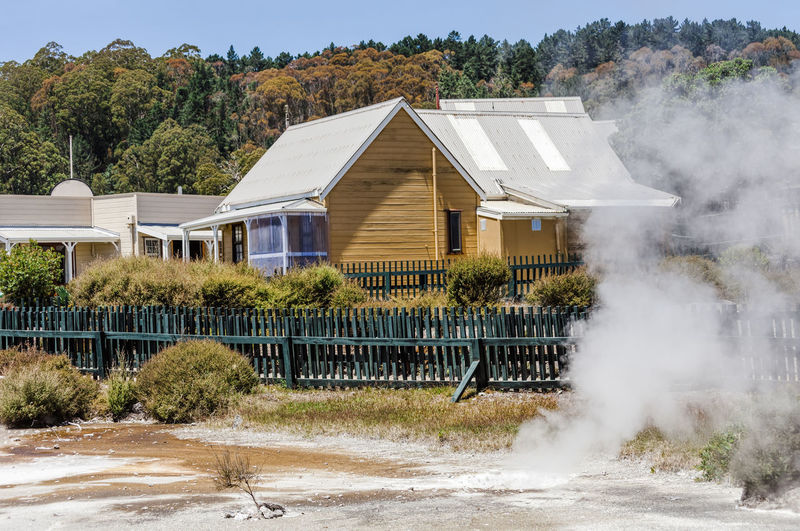 Steam rising from geothermal pool in front of Maori village in Rotorua, New Zealand. Steam Volcanic Landscape Danger Maori Maori Culture Lifestyles Residential Building Residential Structure House Village Whakarewarewa Rotorua  New Zealand Geothermal  Geothermal Activity Fence Hot Pools Geothermal Pools Active Volcano Volcanic Activity Town RISK Heat - Temperature Tourist Attraction  Extreme Terrain Architecture Building Exterior Tree Built Structure Plant Building No People Day Nature Growth Smoke - Physical Structure Residential District Land Water Outdoors Sky Sunlight Luxury