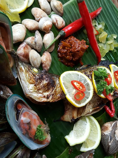 Fried Fish And Animal Shells On Banana Leaf
