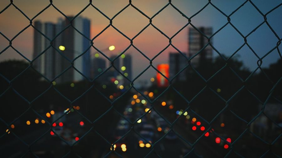 "The City Light "" The city is never sleep "" Chainlink Fence Safety Illuminated Outdoors Focus On Foreground Protection Sky Close-up Security No People Landscape Like Followme Follow4follow Instagram Respost EyeEm Best Shots EyeEm Gallery Fujifilm Terfujilah Fujifilm_xseries 50mm Bokeh Bokeh Lights"