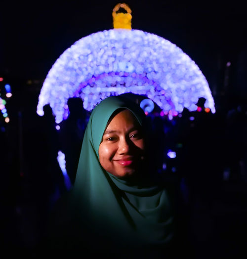 Portrait Of Smiling Young Woman In Hijab Against Illuminated Decoration