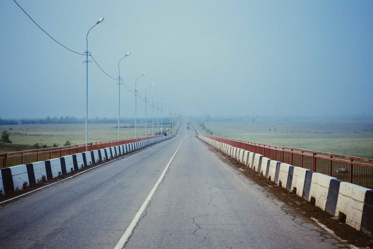 Empty road amidst field against clear sky during foggy weather