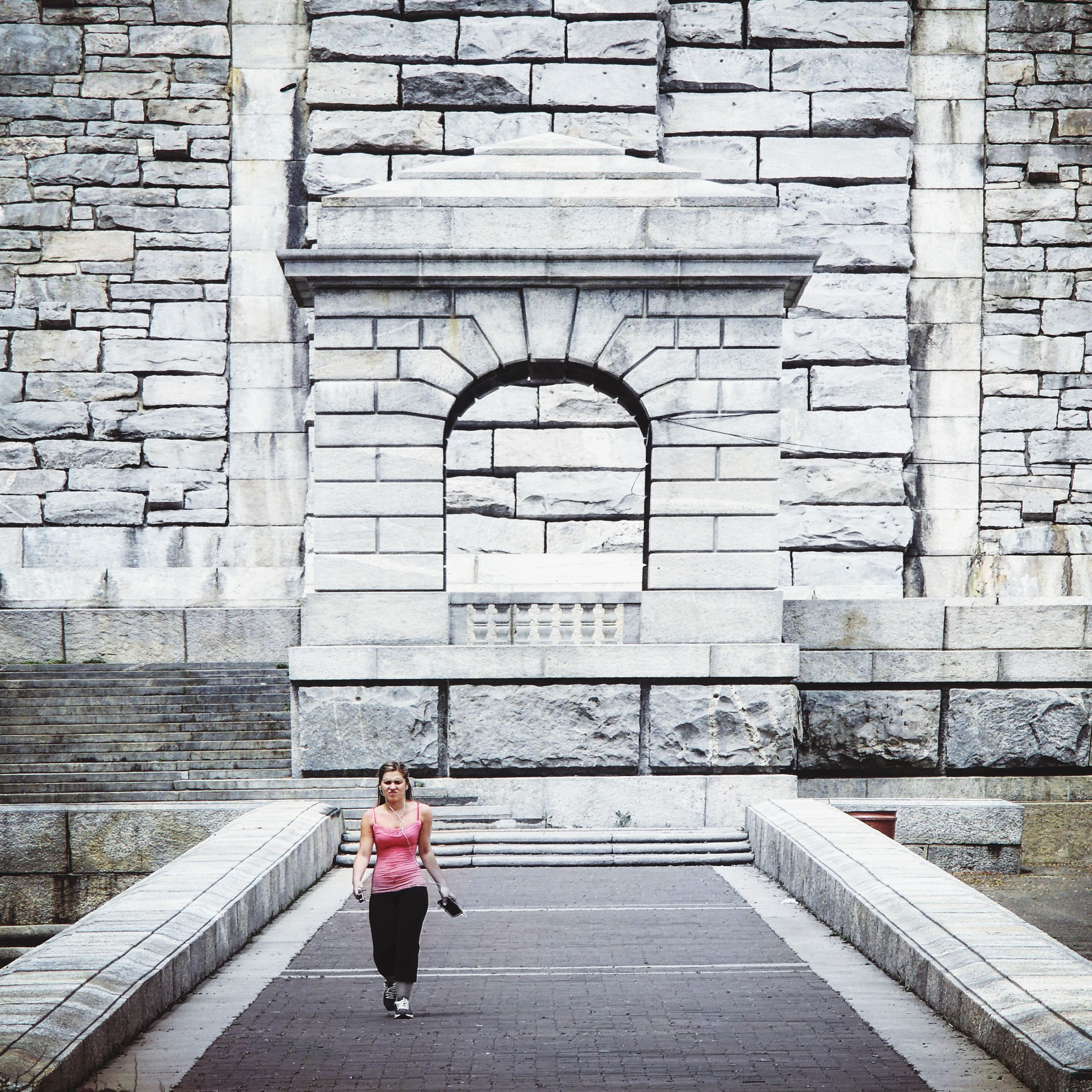 full length, walking, architecture, arch, built structure, lifestyles, casual clothing, leisure activity, steps, day, history, person, outdoors, in front of, stone material, the past, architectural feature, arched, young adult