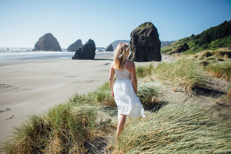 Rear View Of Young Woman Walking At Beach