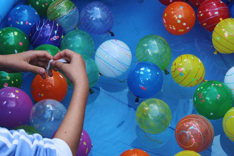Cropped Hands Of Boy Holding Balloon In Wading Pool