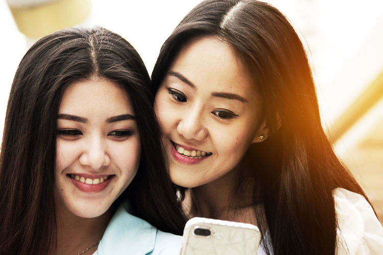 Close-Up Of Smiling Friends Using Smart Phone In City