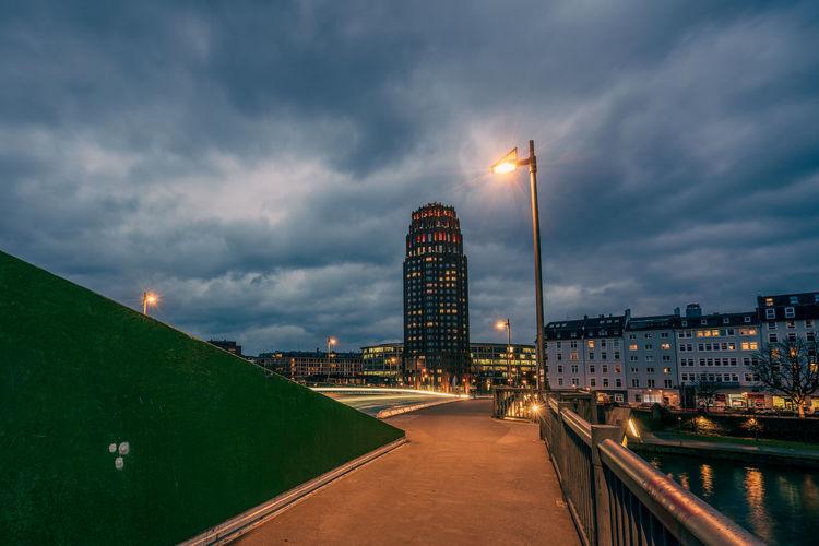 Illuminated buildings against cloudy sky