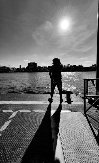 Rear view of silhouette man standing by sea against sky