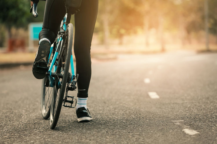 Low section of woman riding bicycle on road