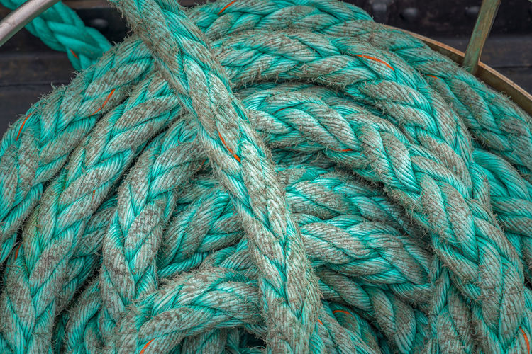 Directly above shot of turquoise rope rolled on boat