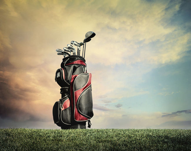 Red and black golf bag with clubs on grass against dramatic clouds Golf Clubs Grass Clouds Dramatic Filtered Artistic Hill Low Angle View Sky Driver Irons Putter Bag Sunny Green Color Image Photography Nobody Sports Equipment High Contrast Shadow Cloud - Sky Sunset Outdoors Golf Bag