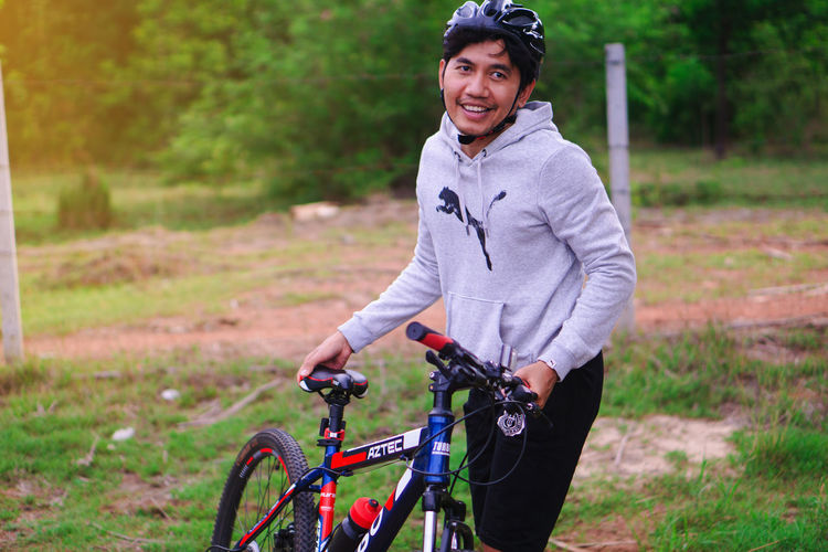 Portrait of young man riding bicycle on field