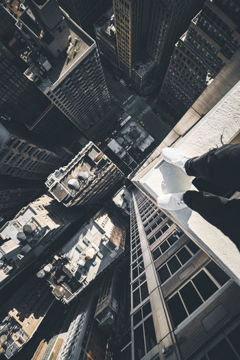 Low section of person standing on building in city