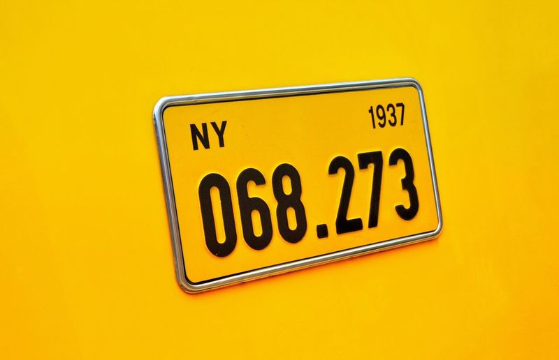 Close-up of information sign against yellow background