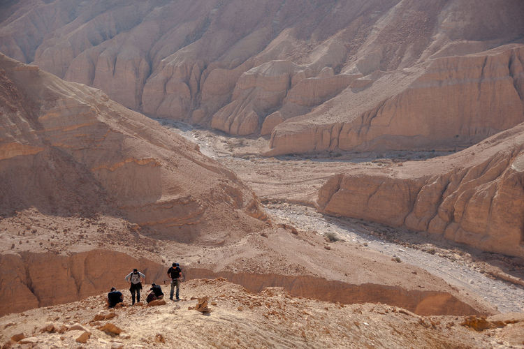 People walking on desert against mountains