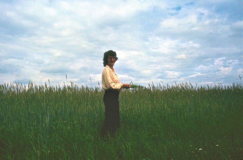 Side view portrait of woman standing on wheat field against sky
