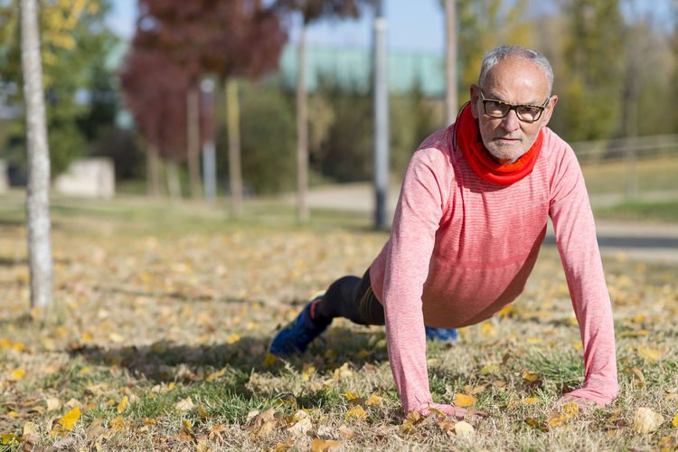 Portrait of a senior man stretching outdoors after jogging Adult Day Effort Exercising Eyeglasses  Focus On Foreground Front View Glasses Healthy Lifestyle Leisure Activity Lifestyles Males  Men One Person Outdoors Plant Real People Senior Adult Senior Men Vitality