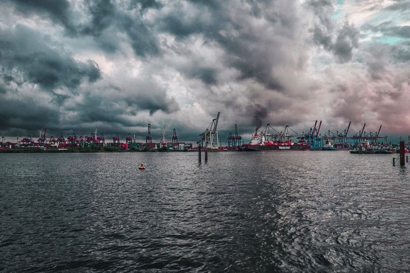Panoramic view of harbor against dramatic sky