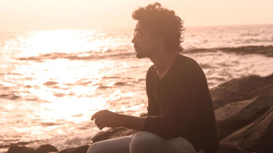 Man sitting on rock at beach during sunset