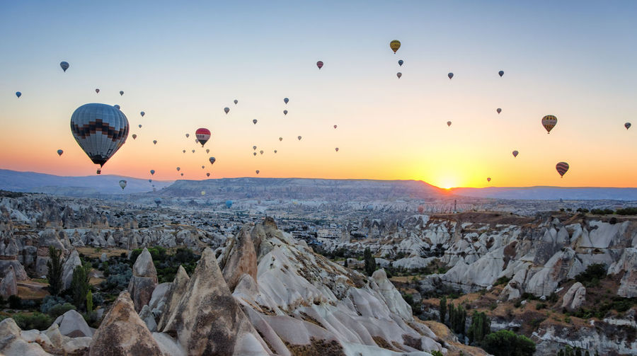 Cappadocia Hot Air Balloons Adventure Ballooning Festival Beauty In Nature Day Flying Hot Air Balloon Landscape Mid-air Mountain Multi Colored Nature No People Outdoors Rock - Object Rock Formation Rock Hoodoo Scenics Sky Sunrise Sunset Travel Destinations