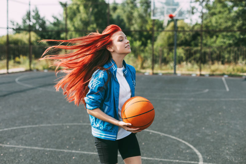 A young basketball player is training on an outdoor basketball court